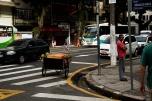 O olhar desatento do vendedor de coco pro seu carrinho, mas, atento ao movimento da rua.